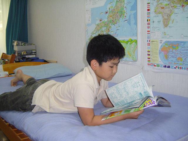 おにいちゃんの部屋で雑誌を読む下の子