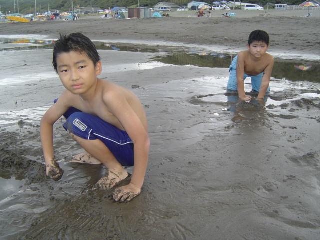浜辺で砂遊びする子供達