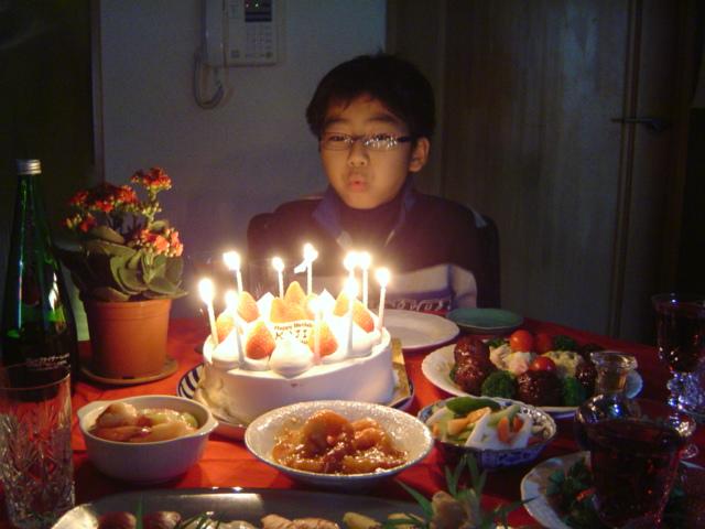 お誕生日ケーキのローソクを吹き消すおにいちゃん