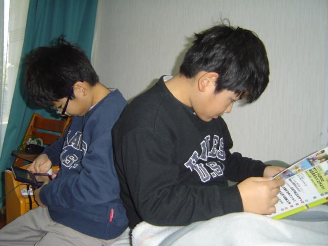 ベッドに並んでゲームするおにいちゃんと「科学」を読む下の子