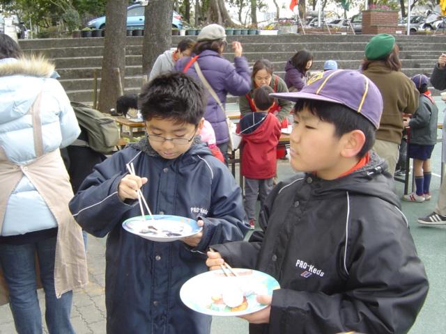 ボーイスカウトの餅つき会にて餅を焼いて食べる子供達