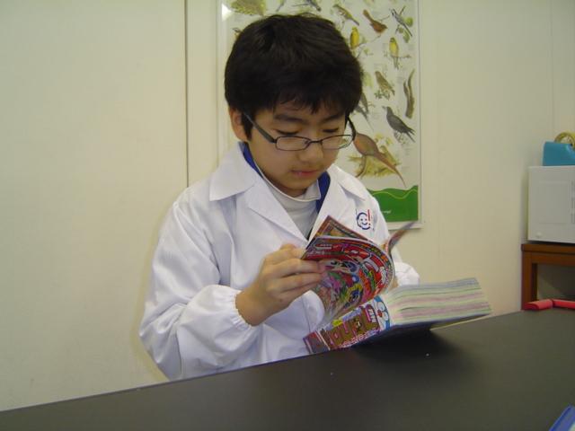 理科教室にて白衣姿で「コロコロ・コミック」を読むおにいちゃん